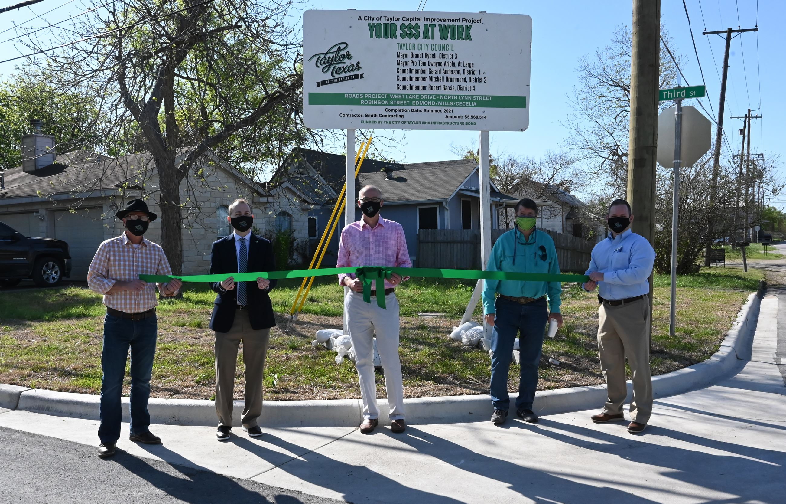 City officials and staff cut a ribbon at Third Street to celebrate completion of reconstrcution